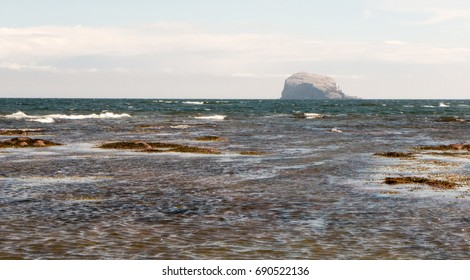 Bass Rock with crashing waves in the foreground on a windy summer's day.