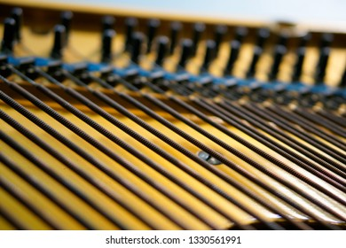 Bass strings strung in the old piano. The mechanism of musical instruments. Closeup. Shallow depth of field