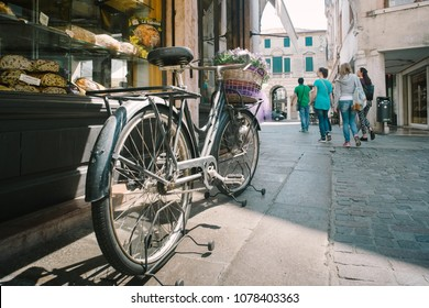 Bassano del Grappa, Italy - 22 April 2018: Montevecchio square. Old bicycle in front of a bakery window
