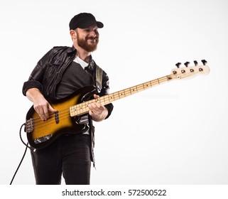 Bassist plays bass guitar. Neutral background
