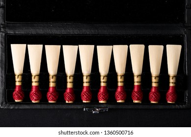 Bassoon reeds inside a box on a black background.