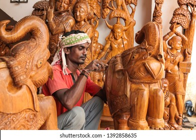 Bastar, 22, October, 2012:  Tribal craftsman in traditional dress  finishing handmade  carved  wooden elephant with other sculptures  displayed in background,   Bastar, Chhattisgarh, India, Asia