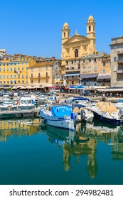 BASTIA PORT, CORSICA ISLAND - JUL 4, 2015: reflection of buildings and cathedral Joannis Babtistes in Bastia port on sunny summer day