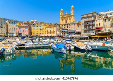 BASTIA PORT, CORSICA ISLAND - JUL 4, 2015: reflection of buildings and cathedral Joannis Babtistes in Bastia port on sunny summer day.