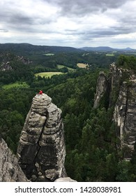 the bastion rocks of Saxon Switzerland in Germany with a climber resting after ascent against clouds in the background