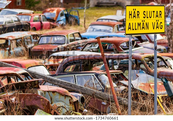 Bastnas, Sweden, April 4, 2020:  Lots of old abandoned vintage cars left in nature at the end of the road in Ivan's Junk Yard - a deserted Swedish car cemetery far out in the woods.