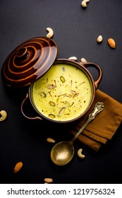 Basundi Or Rabri is an Indian sweet popular in Gujarat and Maharashtra. It is a sweetened condensed milk. Garnished with Dry fruits and Saffron. Served in a bowl over moody background. Selective focus
