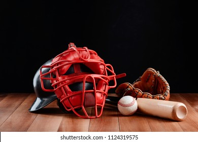 Bat, ball, helmet and mitt. Player's equipment and protection items on wooden table. Baseball, American sport.