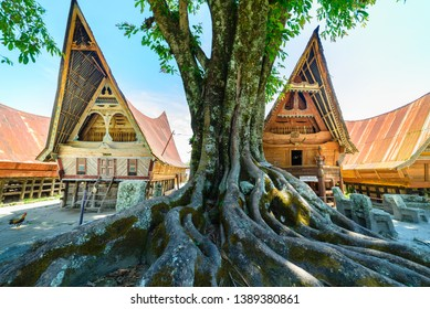 Batak traditional houses in a row, tree root in the foreground, teal orange look. Ambarita village, lake Toba, travel destination in Sumatra, Indonesia.