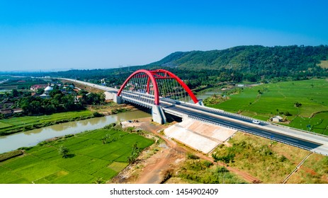 Batang, Central Java / Indonesia - July 1, 2019: Scenic Aerial View of Kalikuto Bridge, an Iconic Red Bridge at Trans Java Toll Road