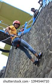 Batang, Jawa Tengah, Indonesia - November 4 2016  The girl rappelling down the rock wall