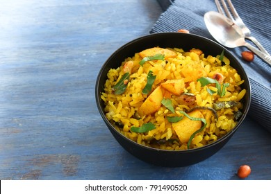 Batata Poha / Indian breakfast with potatoes and flattened rice, selective focus
