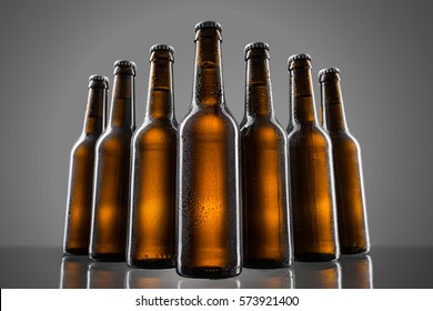 Batch of beer bottles over dark grey background. Wet glass with condensed water-drops. Cool element for advertisement.