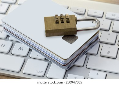 Batch of Credit or debit Cards with a combination lock on a modern silver keyboard