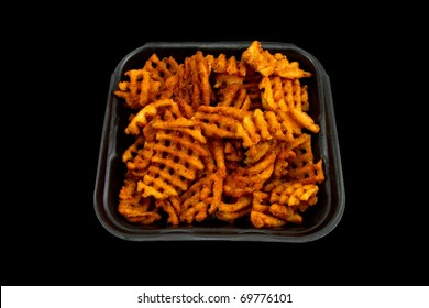 A Batch of Mesquite Barbeque Waffle Fries Isolated on a Black Background