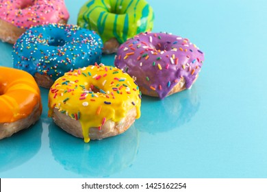 A Batch of Rainbow Colored Glazed Donuts