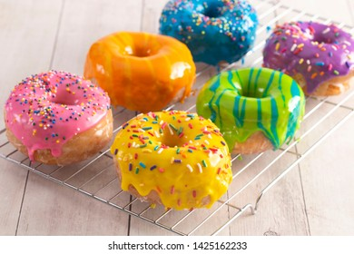 Batch of Rainbow Donuts on a White Wood Table