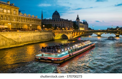 Bateau Mouche cruising on Seine river at sunset, Paris.