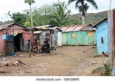 """Batey 106 / Dominican Republic - May 05 2017: """"A family sits outside their painted tin home. Rustic tin and weathered wood houses fill the poverty stricken neighborhood in the sugar cane fields."""