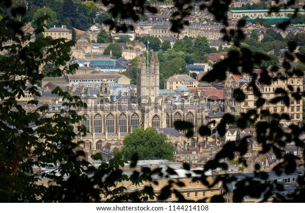 Bath Abbey seen through trees from a high viewpoint above the City of Bath in England
