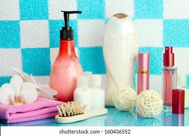 Bath accessories on shelf in bathroom on blue tile wall background