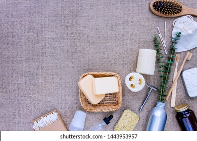 Bath accessories, personal care products in reusable packages. Loofah, bamboo teeth brushes, wooden ear sticks, deodorant crystal, powder on burlap background. Say no to plastic. Zero waste concept.