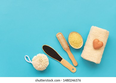 Bath accessories: towel, salt, brush, wisp, pumice and soap on blue background. Spa cosmetic or hygiene concept. Copy space. Flat lay. Top view. Flat lay