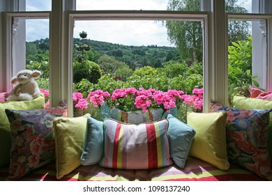 Bath, Avon/England: May 30th 2012: A leafy green view from a window, with colourful cushions and a toy sheep lining a bench seat inside