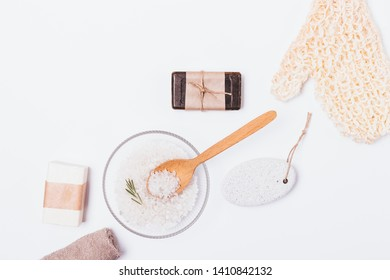 Bath background of cosmetics and accessories for skin cleansing and exfoliation. Flat lay arrangement of massage mitten washcloth, soap, sea salt, pumice and towel on white table.