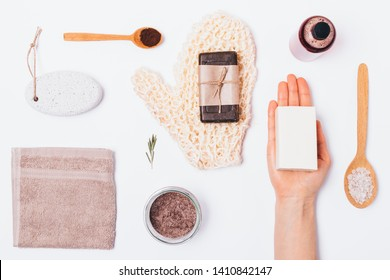 Bath background in knolling style. Flat layout of items and beauty products for cleansing and exfoliating body skin. Top view massage washcloth, coffee scrub and soap on white table.