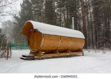 Bath barrel on the background of a winter coniferous forest. The first  snow is falling. Health care