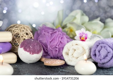 Bath bomb, orchid flowers, burning candles, towel, soap, washcloths, combs, abstract lights Spa resort therapy composition Soft focus