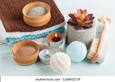 Bath bombs and moroccan clay powder, spa composition with brush and lit candles on white background