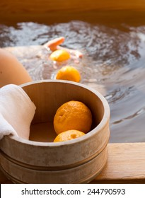 Bath bucket with fruits of yuzu during traditional yuzu bathing at Japanese onsen. This bath also known as yuzuyu and yuzuburo, taken during winter solstice, a custom that dates to early 18th century.