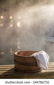 Bath bucket with a towel at blurred and fogged hot spring bath at Japanese onsen. Shot in the light of rising sun.