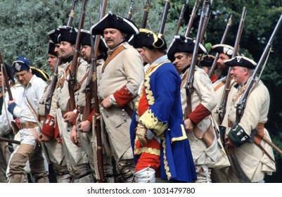 Bath England 2001. Reenactors of the French Indian Wars wear the period uniforms and Flintlock muskets of French Fusiliers 1760 recreate a battle at a re-enactment event.