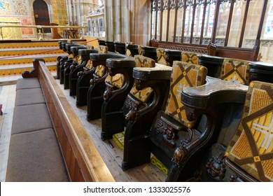 Bath England May 2017. A fine example of a row of miseriecord or mercy seat with deep carving and tapestry cushions in church. Seats in upright position showing shelf seat.