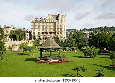Bath England Nay 2017. Parade Gardens. Looking across green sword to six story Bath stone flats. Bandstand in park surrounded by flowers. Trees in leaf. One deck chair. High white cloud.