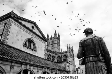 Bath (England, UK) Stone statue of the roman in Antique Roman Baths complex, flying birds in sky and Abbey Cathedral at background. City of Bath is a UNESCO World Heritage Site. Black and white photo.