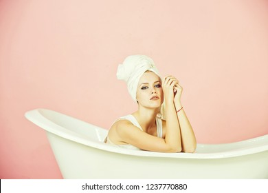 bath. girl with towel turban on head sitting in white bathtub on pink background, spa and beauty, relax and hygiene, healthcare and housekeep, copy space
