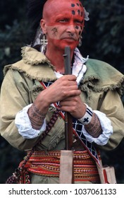 Bath Museum England 2002. An unidentified re-enactor of the French Indian Wars 1760 he wears the period clothing of a native American Mohawk Indian and stands wearing face paint and holding a musket.