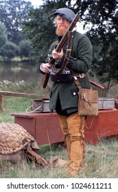 Bath Museum England June 2001. A reenactor wearing the period uniform of a ranger in the French Indian Wars holding a flintlock musket at a re-enactment in a woodland setting.