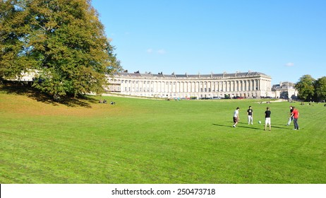 BATH - OCT 17: People gather in the warm sun in Victoria Park at the landmark Royal Crescent on Oct 17, 2010 in Bath, UK. Bath is a UNESCO World Heritage city with 4.5 million visitors a year.
