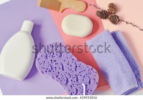 Bath products for bathroom. Natural cosmetic products. Shampoo, soap, purple terry towel, sponge and wooden comb. Flat lay beauty photography, top view