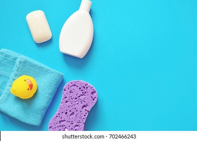 Bath products flat lay. Organic baby soap, white shampoo bottle, towel, purple sponge and yellow rubber duck on a blue background. Top view photography