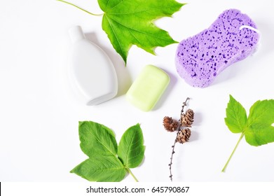 Bath products with green leaves on a white background. Herbal cosmetics. Soap, shampoo and purple sponge. Hair care concept. Flat lay beauty photography