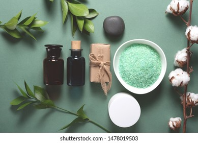 Bath salt, aroma oil bottle, face cream jar and soap on a green background.