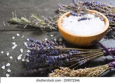 bath salt in bamboo bowl and dried lavender flowers on old black wood table