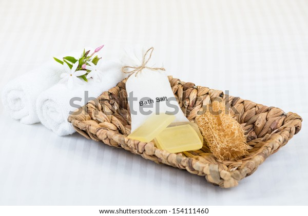 Bath salt in cotton pouch, glycerin soaps, loofah in banana leaf basket on top of white striped cotton bed linen close up