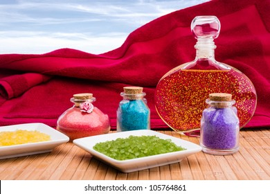 Bath salt and essential oil with sky on background.